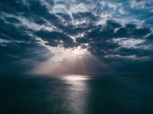 A shaft of light pierces grey-blue clouds illuminating a swath of sea