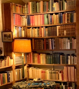 A close up of a set of very full book shelves, with a standard lamp on a table in front of them. The lamp is on, casting a warm glow over the books, all of which look old, many with leather or cloth hardback covers.  It is impossible to tell if all of the books have been read.