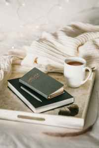 Two notebooks, stacked one on top of the other, sit on a white tray with a cup of coffee  next to them. The tray rests on a bed and cream coloured woven blanket is crumpled up in the background