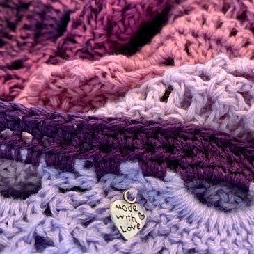 "A crochet shawl in shades of lilac and purple fills the picture. In the centre at the bottom a heart shaped charm in attached to the crochet and it has the words ""made with love"" written on it."