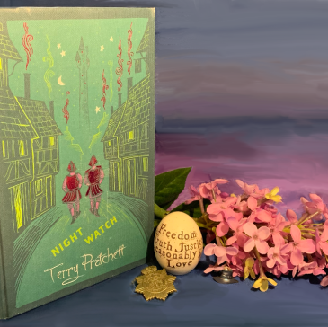 """Photo of the Discworld Collector's version of Night Watch set next to a sprig of lilac, a wooden egg with the words """"Freedom, Truth, Justice, Reasonable Priced Love"""" written on it, a City Watch police badge and a small lapel pin in the shape of Terry's Hat. They are standing against a background painted to look like a lilac shaded sunset."""