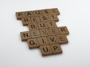 Wooden scrabble tiles sit on a plain white table. They spell out: Pause Rest But Never Give Up
